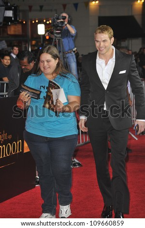 """LOS ANGELES, CA - NOVEMBER 16, 2009: Kellan Lutz, with fan he selected from the crowd to join him at the premiere, at the premiere of """"The Twilight Saga: New Moon"""" at Mann Village & Bruin Theatres - stock photo"""