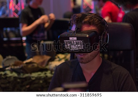 Los Angeles, CA - USA - August 29, 2015: Guy tries Oculus headset during VRLA Expo, virtual reality exposition, event at the Los Angeles Convention Center in Los Angeles. - stock photo