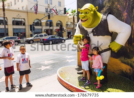 Los Angeles, CA, USA - MAY 27 2013:  Happy kids are taking photos with the movie character Shrek on the sidewalk of famous Hollywood Walk of Fame - stock photo