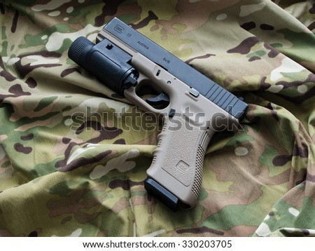 Los Angeles, CA, USA - September 11, 2015: Glock 17 semi-automatic 9x19mm pistol and a Multicam pattern background - stock photo