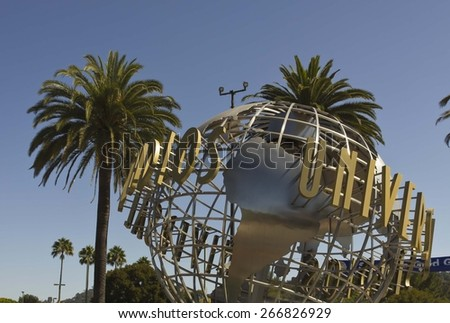 LOS ANGELES, CALIFORNIA - AUG 17 2013: Universal Studios Hollywood sign at the entrance of the amusement Park, suroounded by palms - stock photo