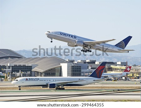 LOS ANGELES/CALIFORNIA - JULY 12, 2015: United Airlines Boeing 777 departs as Delta Airlines Boeing 767 arrives at Los Angeles International Airport in Los Angeles, California, USA - stock photo