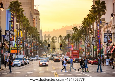 LOS ANGELES, CALIFORNIA - MARCH 1, 2016: Traffic and pedestrians on Hollywood Boulevard at dusk. The theater district is famous tourist attraction. - stock photo