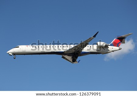 LOS ANGELES, CALIFORNIA, USA - JANUARY 28, 2013 - Delta Connection (Comair) Bombardier CRJ-900 lands at Los Angeles Airport on January 28, 2013. The plane has a range of 2,250 mi with 70 passengers.