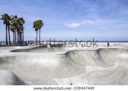 LOS ANGELES, CALIFORNIA, USA - June 20, 2014:  Concrete ramps and palm trees at the popular Venice beach skateboard park in Los Angeles, California. - stock photo
