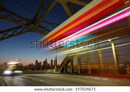 Los Angeles city at night. Long exposure shot of blurred bus speeding through iconic 6th Street Bridge - stock photo