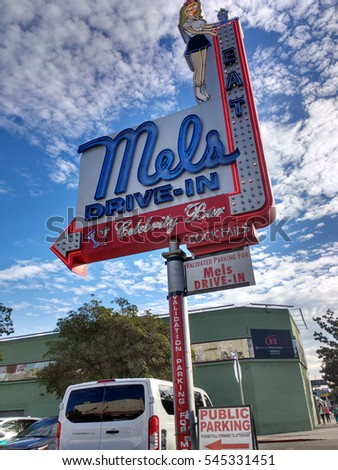 LOS ANGELES, DEC 29, 2016: Close-up against dramatic blue cloudy sky of sign of Mels Drive-In restaurant in Hollywood near Hollywood Boulevard's Walk of Fame.