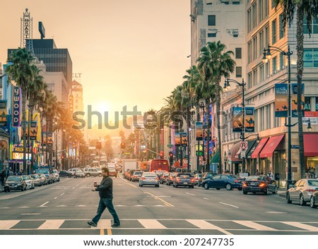 LOS ANGELES - DECEMBER 18, 2013: man crossing the road in Hollywood Boulevard at sunset. The Hollywood Walk of Fame was created on this street as tribute to artists from the entertainment industry. - stock photo
