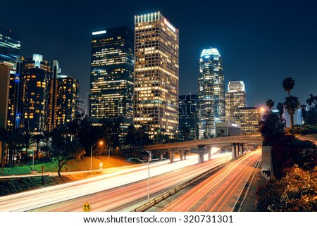 Los Angeles downtown at night with urban buildings and light trail - stock photo
