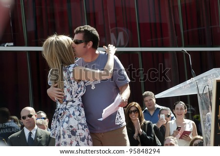 LOS ANGELES - FEBRUARY 22: Actor-comedian Adam Sandler hugs Jennifer Aniston at her Hollywood Walk of Fame Star Ceremony at Hollywood Blvd on February 22, 2012 in Los Angeles, CA. - stock photo