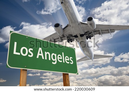 Los Angeles Green Road Sign and Airplane Above with Dramatic Blue Sky and Clouds. - stock photo