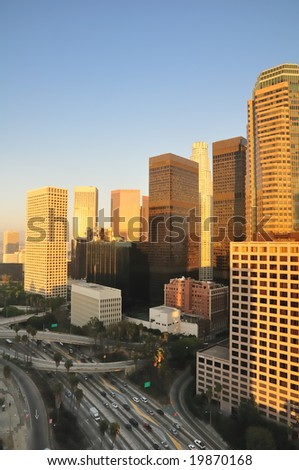 Los Angeles high-rises over a busy freeway at sunset