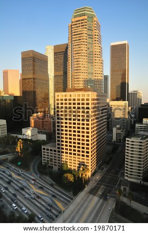 Los Angeles high-rises over a busy freeway at sunset - stock photo
