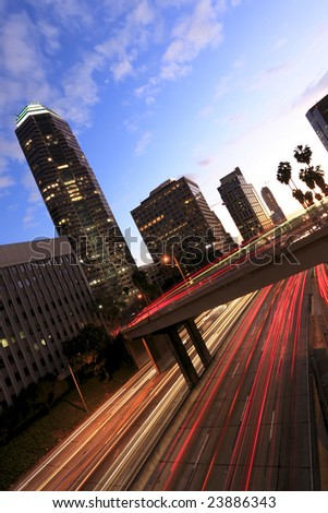 Los Angeles highway at sunset with traffic as trails of light - stock photo