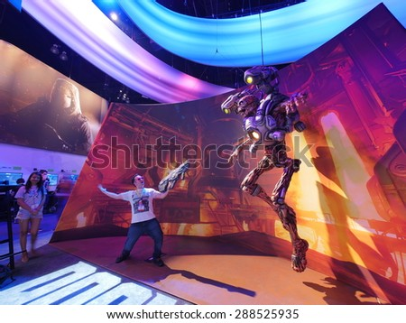 LOS ANGELES - June 17: Man fighting cyborg monster model from DOOM video game at E3 2015 expo. Electronic Entertainment Expo, commonly known as E3, is an annual trade fair for the video game industry - stock photo