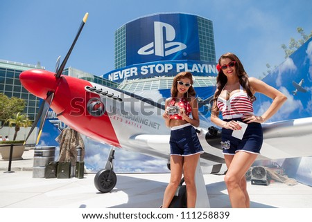 LOS ANGELES - JUNE 8: Pin ups posing for media at the entrance of the show with PlayStation sponsorship in the background during E3 2012, world video games Expo June 8, 2012 in Los Angeles, CA - stock photo