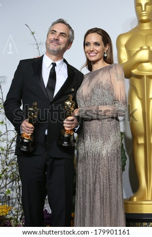 LOS ANGELES - MAR 2:: Alfonso Cuaron, Angelina Jolie  in the press room at the 86th Annual Academy Awards on March 2, 2014 in Los Angeles, California - stock photo