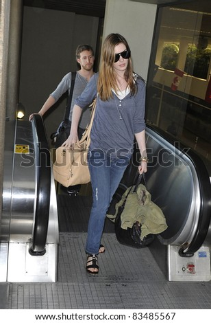 LOS ANGELES-MARCH 30: Actress Anne Hathaway with boyfriend at LAX airport. March 30 in Los Angeles, California 2011