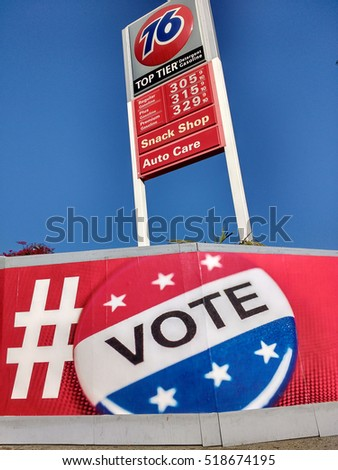 "LOS ANGELES, NOV 13TH, 2016: A large ""Vote"" button mural on red background against the blue sky and the sign of a 76 gas station towering above it in Los Angeles, CA."