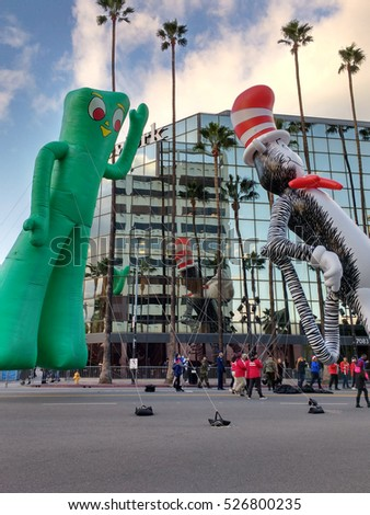 LOS ANGELES, NOV 27TH, 2016: Cat in the Hat and Gumby balloons float tall next to the mirrored windows of an office building alongside Hollywood Boulevard during the 85th Hollywood Christmas Parade.