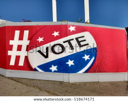 "LOS ANGELES, NOV 13TH, 2016: Close-up of a large ""Vote"" button mural on red background against the blue sky at a gas station in Los Angeles."