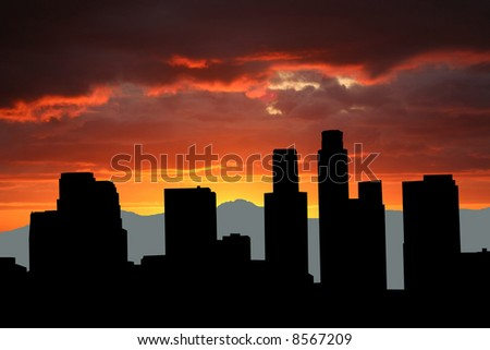 Los Angeles skyline with mountains at sunset - stock photo