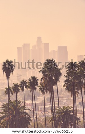 Los Angeles skyline with palm trees in the foreground - stock photo