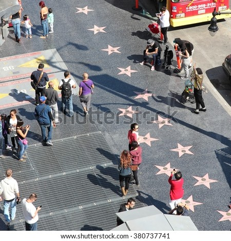 LOS ANGELES, USA - APRIL 5, 2014: People walk famous Walk of Fame in Hollywood. Hollywood Walk of Fame features more than 2,500 stars with inscribed celebrity names. - stock photo