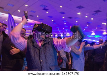 Los Angeles, USA - January 23, 2016: Man tries virtual reality headset and hand controls during VRLA Expo Winter, virtual reality exposition, at the Los Angeles Convention Center. - stock photo
