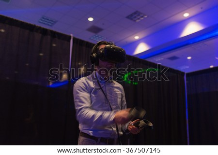 Los Angeles, USA - January 23, 2016: Man tries virtual reality HTC Vive headset and hand controls during VRLA Expo Winter, virtual reality exposition, at the Los Angeles Convention Center. - stock photo
