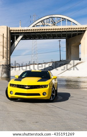 Los Angeles, USA - September 28, 2015: Chevrolet Camaro in Los Angeles river. Historic 6th Street viaduct bridge built in 1932 crossing the L.A. River. - stock photo