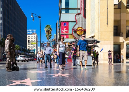 LOS ANGELES, USA - SEPTEMBER 27: Tourists walk on Hollywood Walk of Fame on September 27, 2013 in Hollywood, Los Angeles - California. There are over 2400 celebrity stars on Hollywood Blvd. - stock photo