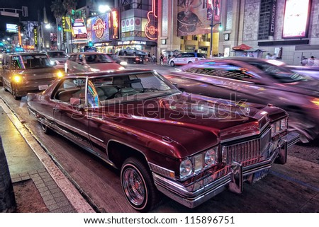 LOS ANGELES, USA - SEPTEMBER 23: Vintage car parked on Hollywood boulevard in LA on September 23, 2012 as night traffic passes by. The sidewalks of this iconic boulevard contain the walk of fame. - stock photo