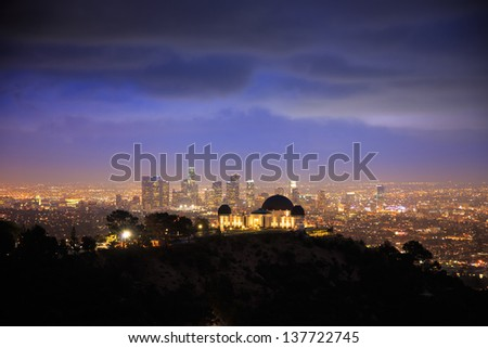 Los Angels city skyline at night with Griffith Observatory in foreground and downtown in background. - stock photo
