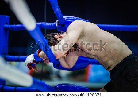 loser of fight boxer on ropes of corner ring after fight - stock photo