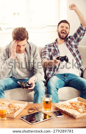 Losers and winners. Two young men playing video games while sitting on sofa - stock photo