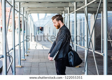 Lost. American man with beard, mustache traveling in New York, wearing black shirt, shoulder carrying leather bag, stands on sidewalk bridge, lowers head, sad, thinks. Filtered look with blue tint.