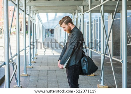 Lost.  American student with beard, mustache studying in New York. Business man, shoulder carrying leather bag, holding laptop computer, standing on sidewalk bridge, lowering head, sad, thinking.