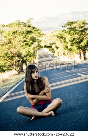 Lost beautiful girl in the middle of the road - stock photo