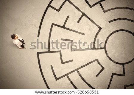 Lost business man looking for a way in circular labyrinth concept