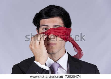 Lost businessman peeking behind a blindfold - stock photo