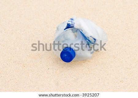 lost compacted plastic bottle on a beach - stock photo