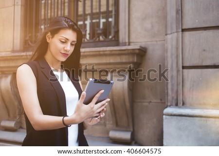 Lost female tourist is using digital tablet for navigation while is walking in urban setting during summer holidays, latin woman wanderer viewing photos that she took on her touch pad during strolling - stock photo