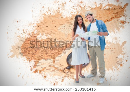Lost hipster couple looking at map against world map with compass showing north america - stock photo