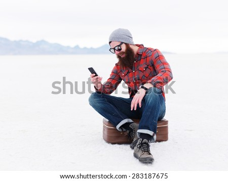 lost hipster with beard with suitcase using smartphone on salt flats - stock photo