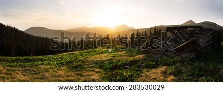 Lost house in hills in mountains at spring. Panoramic. - stock photo