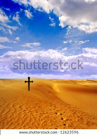 Lost in a Desert. Footprints leading to a Cross in the searing Heat during a Sandstorm in the Dunes of Dubai - stock photo