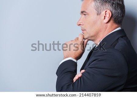 Lost in business thoughts. Side view of thoughtful mature man in formalwear holding hand on chin and looking away while standing against grey background - stock photo