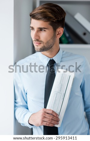 Lost in business thoughts. Thoughtful young man in shirt and tie holding newspaper and looking through a window while standing in office - stock photo
