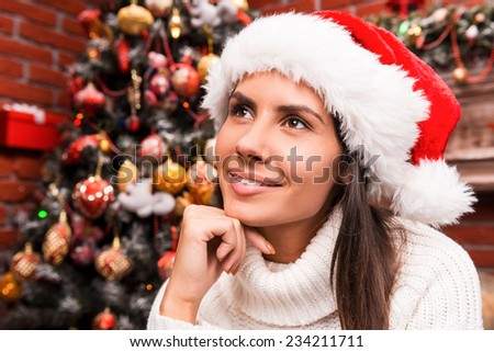 Lost in Christmas thoughts. Thoughtful young woman in Santa hat holding hand on chin and looking away while sitting in front of the Christmas Tree  - stock photo